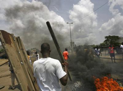 Demonstranten haben in Abidjan aus brennenden Autoreifen Straßensperren errichtet.