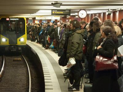 Fahrgäste warten im U-Bahnhof Alexanderplatz in Berlin dicht gedrängt auf eine Bahn.