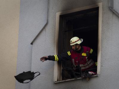 Ein Feuerwehrmann wirft nach einem Brand einen Gegenstand aus dem Unglückshaus.