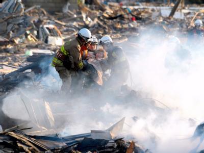 Rettungskräfte in Natori holen Überlebende aus den Trümmern: Die verwüstete Stadt liegt in der Katastrophenregion Miyagi