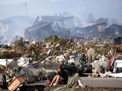 In der Stadt Natori sitzt eine Frau zwischen Trümmern.