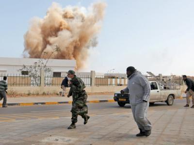 Libysche Rebellen verlassen nach einem Luftangriff der lybischen Luftwaffe in der Stadt Ras Lanuf ihre Stellungen.