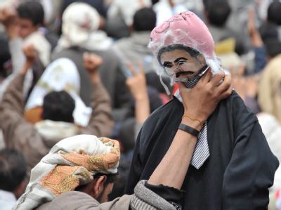 Ein Demonstrant in Sanaa mit einem Abbild des Präsidenten Ali Abdullah Saleh.