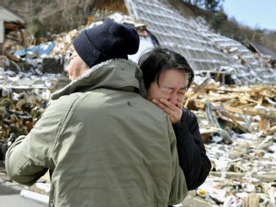 Weinend liegt sich ein älteres Paar in der Stadt Onagawa im Nordosten Japans in den Armen. Foto:Kyodo