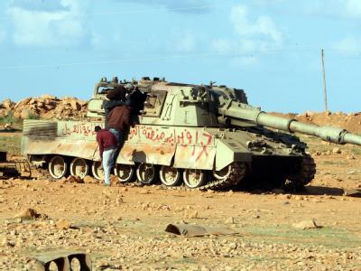 Libysche Rebellen inspizieren einen zerstörten Panzer der Gaddafi-Truppen.