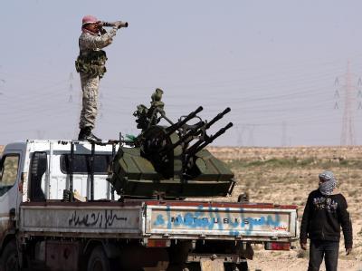 Ein Aufständischer steht mit einem Fernrohr auf einer Flak. Die Allianz will die Streitkräfte von Machthaber Gaddafi jetzt außerhalb der Städte angreifen.