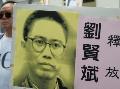 Ein Demonstrant einer Menschenrechtsgruppe hält bei einer Demonstration in Hongkong ein Poster des chinesischen Dissidenten Liu Xianbin.