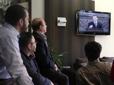 Syrer verfolgen die Rede ihres Präsidenten im Fernsehen.
