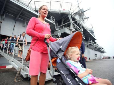 Eine Touristin verlässt mit ihrem Baby ´den thailändischen Flugzeugträger, der sie in Sicherheit gebracht hatte.