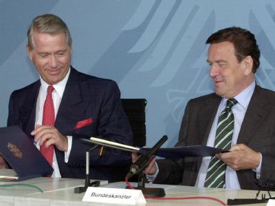 Bundeskanzler Gerhard Schröder (SPD) und der damalige eon-Vorstandsvorsitzende Ulrich Hartmann (l.) tauschen die Grundsatzvereinbarung über den Ausstieg aus der Atomenergie am 11.06.2001 im Berliner Kanzleramt aus.
