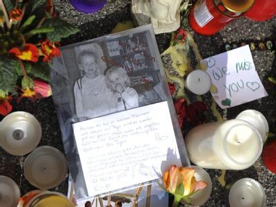 Blumen und Kerzen sowie ein Foto vor dem Haus in Krailling in dem zwei Geschwister grausam ermordet wurden.