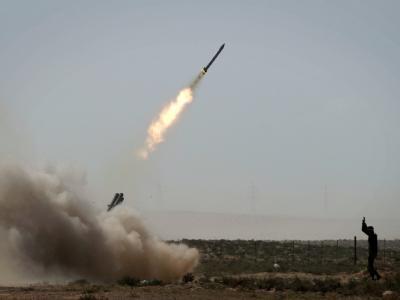 Aufständischen feuern Raketen in Richtung der gaddafitreuen Truppen ab.