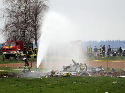 Feuerwehrleute löschen bei Laufeld die Trümmer des abgestürzten US-amerikanischen Militärflugzeugs.