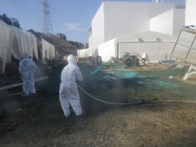Helfer sprühen Kunstharz auf dem Gelände des havarierten Atomkraftwerkes im japanischen Fukushima aus, um radioaktiven Staub zu binden.