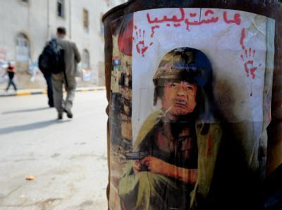 Ein Mann geht in Bengasi an einem Anti-Gadaffi-Bild vorbei.