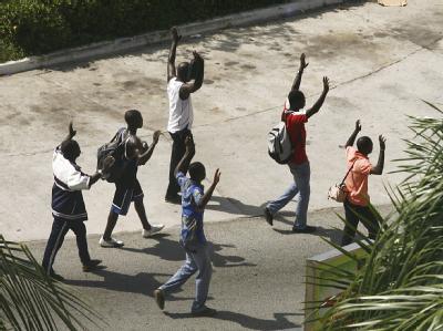 Mit erhobenen Armen: Zivilisten in der umkämpften Hafenstadt Abidjan.