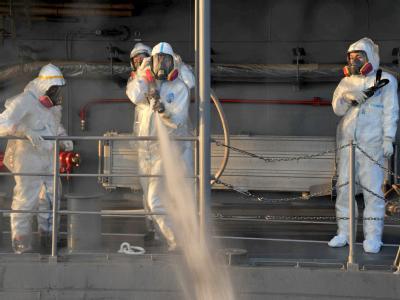 Mitarbeiter der japanischen Marine arbeiten von einem Schiff von der Meeresseite aus an den havarierten Atomkraftwerk Fukushima.