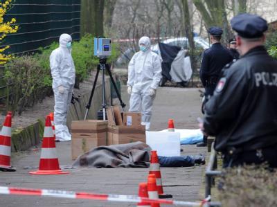 Beamte der Spurensicherung dokumentieren im Hamburger Stadtteil Hamm nach einer Schießerei den Tatort mit einer Spezialkamera.