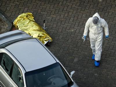 Eine abgedeckte Leiche liegt auf dem Parkplatz vor dem Einkaufszentrum: Sieben Tote, 17 Verletzte - und noch ist kein Motiv erkennbar.