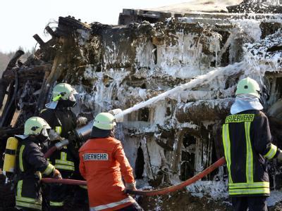 Nach der Massenkarambolage besprühen Feuerwehrleute den letzen ausgebrannten LKW.