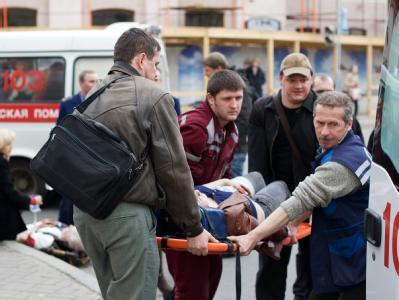 Rettungskräfte und Passanten tragen einen Verletzten in Minsk zu einem Rettungswagen.