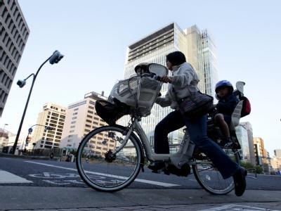 Eine japanische Mutter fährt mit ihrem Kind durch Tokio.