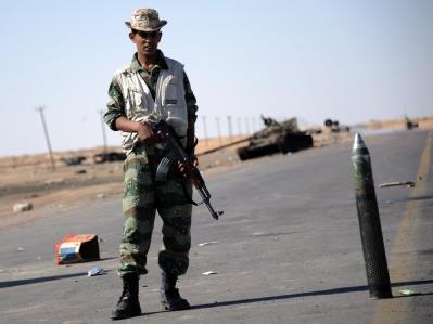 Ein libyscher Oppositionskämpfer bewacht einen Kontrollpunkt an der Straße zwischen Brega und Adschdabija.