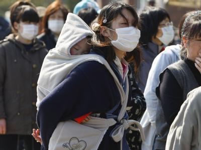 Eine Mutter steht mit ihrem Kind an, um im Hilfslager in der Stadt Onagawa Essen zu bekommen.