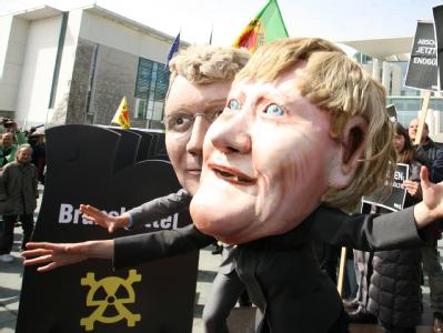 Bundeskanzlerin Angela Merkel und Bundesumweltminister Norbert Röttgen aus Pappmarché: Atomkraftgegner machten am Freitag vor dem Kanzleramt in Berlin ihrem Ärger Luft.