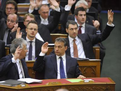 Ungarns Ministerpräsident Viktor Orban (vorne r.) und Abgeordnete seiner Partei Fidesz stimmen im Parlament in Budapest für die neue Verfassung.