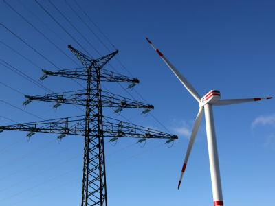 Windkraftanlage vor Hochspannungsleitung