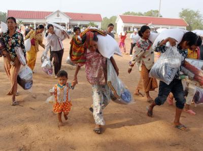 Fliehende Kambodschaner tragen Lebensmittel und persönliche Habe aus dem Kampfgebiet.