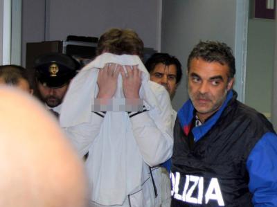 Der gescheiterte Flugzeugentführer aus Kasachstan verlässt in Begleitung der Polizei Roms Flughafen Fiumicino.