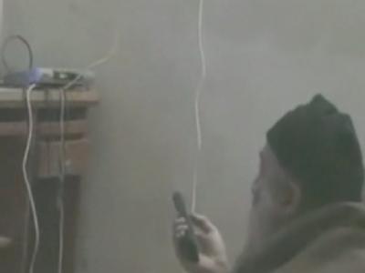 Die Szene aus einem vom Pentagon freigegebenen Video zeigt Osama bin Laden vor einem Fernseher mit einer Fernbedienung in der Hand.