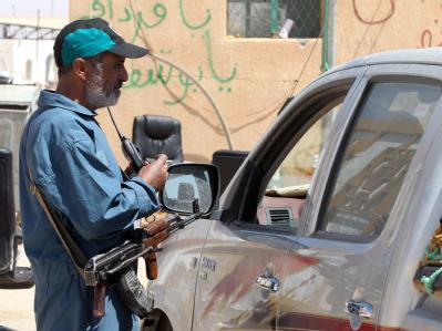 Ein libyscher Aufständischer kontrolliert am Grenzposten Wassin ein Auto.