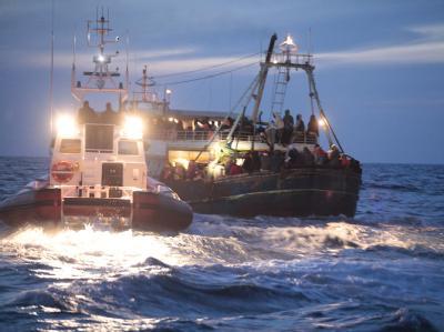 Die italienische Küstenwache nimmt ein Schiff mit libyschen Flüchtlingen in Empfang.