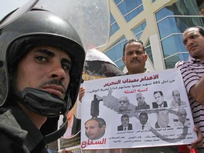 Demonstranten und ein ägyptischer Polizist stehen vor den Gerichtsgebäude, in dem der Prozess gegen den ehemaligen Innenminister Habib al-Adli stattfindet.