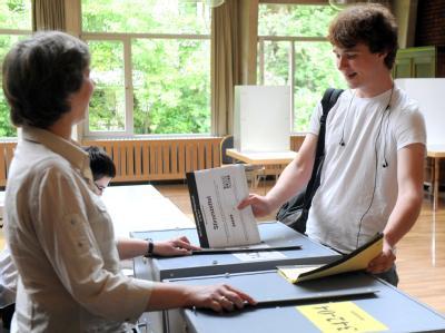 Der Schüler Julian Burmester wirft seine beiden Stimmzettelhefte zur Bürgerschaftswahl in Bremen in zwei entsprechend gekennzeichnete Wahlurnen.