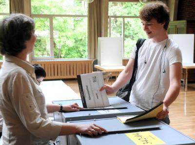 Der Schüler Julian Burmester wirft seine beiden Stimmzettelhefte zur Wahl in Bremen in die Urnen. Julian ist im März 16 Jahre alt geworden und darf nach der neuen Wahlordnung zum ersten Mal an der Bürgerschaftswahl teilnehmen.