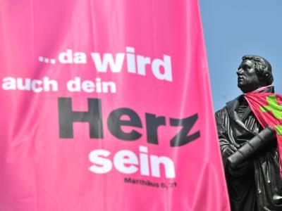 Eine Fahne mit dem Motto des Evangelischen Kirchentages neben einer Statue von Martin Luther.