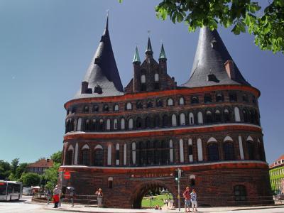 Passanten laufen am Holstentor in Lübeck vorbei. 17 Patienten haben sich möglicherweise in einem Restaurant in der Hansestadt infiziert.