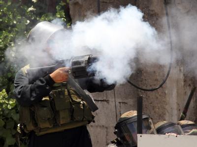 Ein israelischer Polizist feuert ein Tränengas-Geschoss ab.