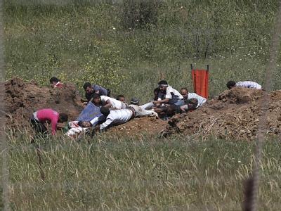 Palästinenser ziehen einen verwundeten Mann hinter einen Erdwall.