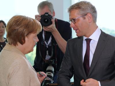 Bundeskanzlerin Angela Merkel und Bundesumweltminister Norbert Röttgen unterhalten sich zu Beginn der Sitzung des Bundeskabinetts im Kanzleramt.