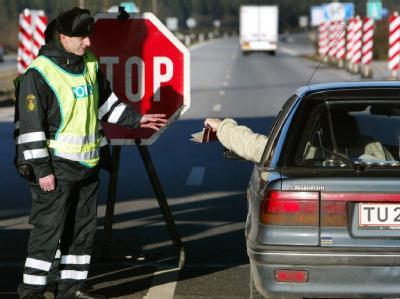 An der deutsch-dänischen Grenze bei Padborg/Froeslev kontrolliert am 10.12.2002 ein dänischer Grenzpolizist die Papiere eines einreisenden Autofahrers.
