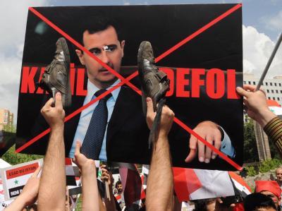 Gegner von Syriens Präsidenten Bashar al-Assad bei einer Protestkundgebung in der türkischen Hauptstadt Ankara. «Verschwinde du Mörder» heißt es auf dem Plakat in türkischer Sprache.