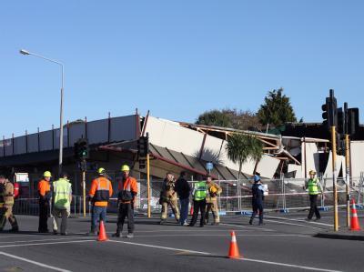 Rettungskräfte stehen vor einem eingestürzten Gebäude in Christchurch.