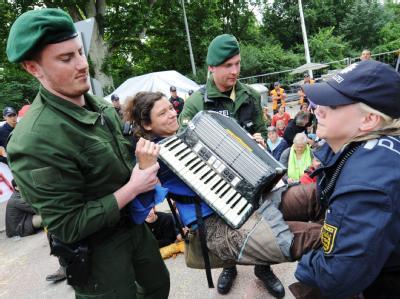 Eine Stuttgart 21-Gegnerin mit Akkordeon wird von Polizisten aus einer Blockade getragen.
