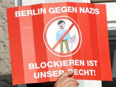 Ein Demonstrant hält in Berlin bei einer Gegendemonstration zu einer NPD-Kundgebung ein Protestplakat.