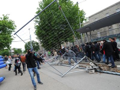Ein Projektgegner reißt einen Bauzaun der Baustelle von Stuttgart 21 ein.